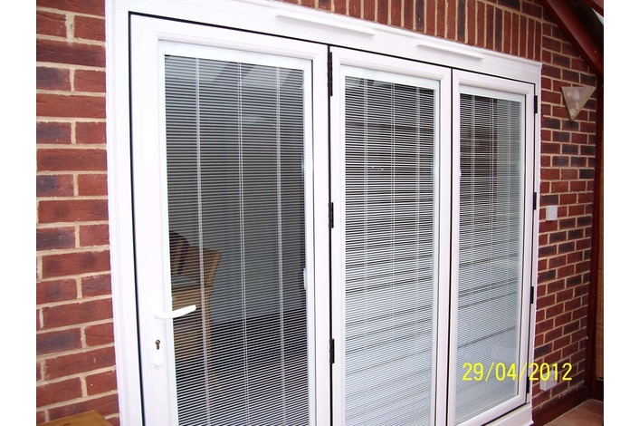 White upvc bifold door with blinds