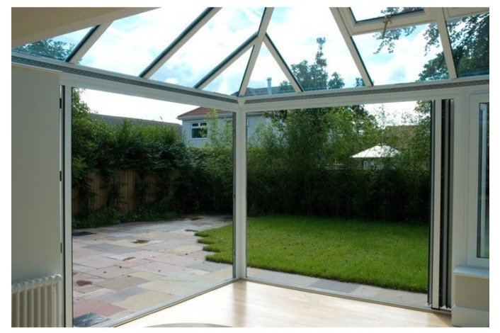 Convervatory featuring white-framed bi-folds - looking out to the garden area.