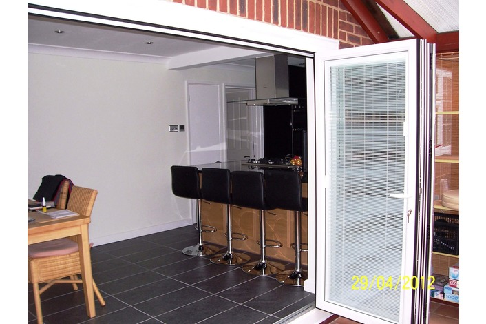 Bi-folds leading to kitchen/bar area.