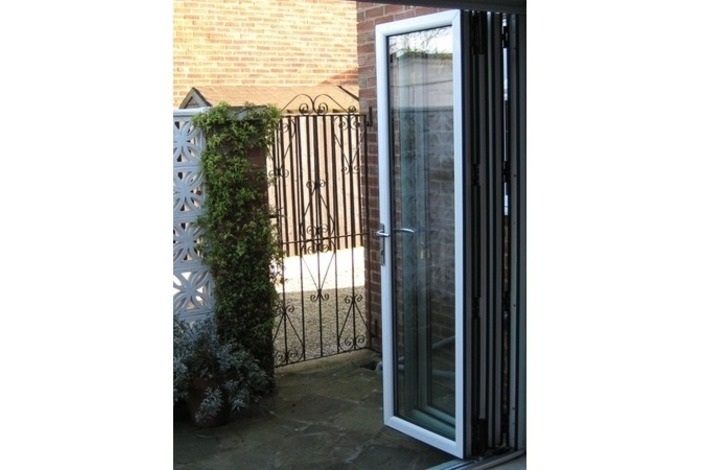 White-framed bi-fold doors leading to gate.