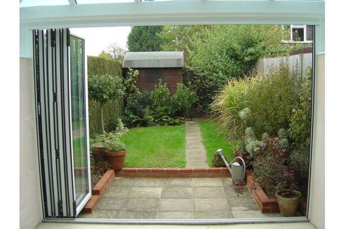 Bi-folding doors leading to a small tidy garden.