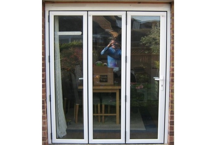 External view of a Timberlook PVCu 3 panel folding sliding door showing the traffic door on the right.  All 3 panels of this bifold will fold and slide to the left.