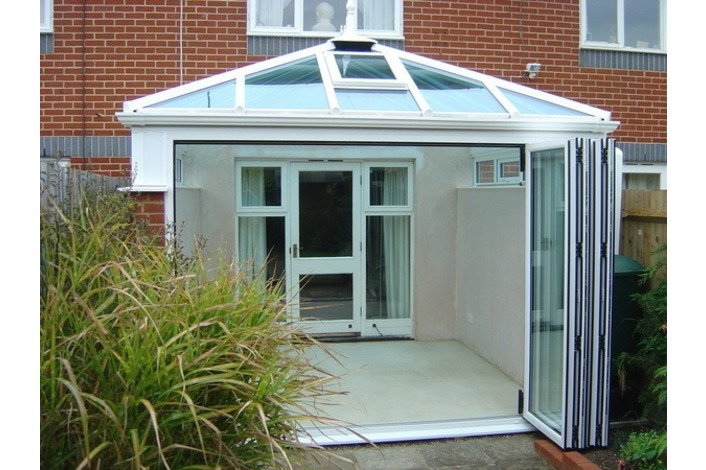 Open white-frame conservatory bi-folding doors.
