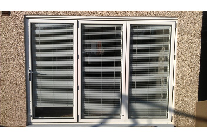 White Visofold 1000 folding door fitted with blinds.