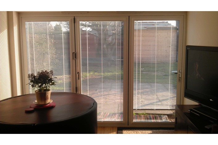 Internal view of a white Visofold 1000 aluminium bifold door with blinds fitted by customer.