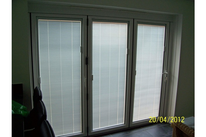 White upvc folding doors with integral blinds fitted.