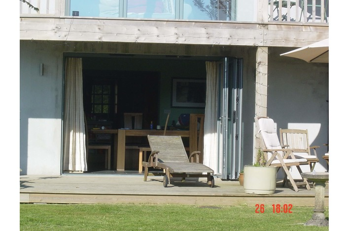 Bi-fold doors leading onto wooden decking - close up