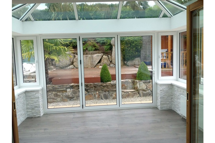 White aluminium bifold doors fitted in a conservatory also supplied by us.